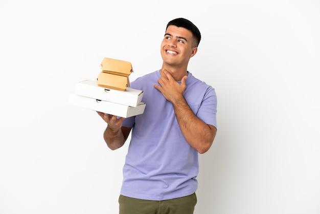 웃고 있는 동안 올려다보는 외진 흰색 배경 위에 피자와 햄버거를 들고 있는 젊고 잘생긴 남자