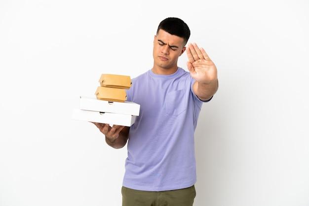 Молодой красавец держит пиццу и гамбургеры на изолированном белом фоне, делая жест стоп и разочарованный