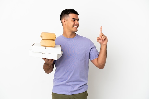 Молодой красавец держит пиццу и гамбургеры на изолированном белом фоне, указывая на отличную идею