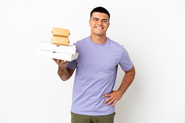Молодой красавец, держащий пиццу и гамбургеры на изолированном белом фоне, позирует с руками на бедрах и улыбается