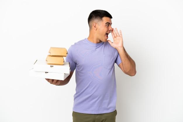 Молодой красавец, держащий пиццу и гамбургеры на изолированном белом фоне, кричит с широко открытым ртом в сторону