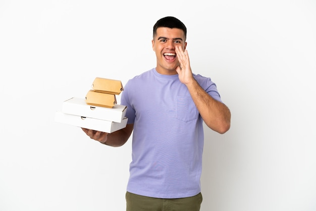 격리된 흰색 배경 위에 피자와 햄버거를 들고 입을 크게 벌리고 소리치는 젊고 잘생긴 남자