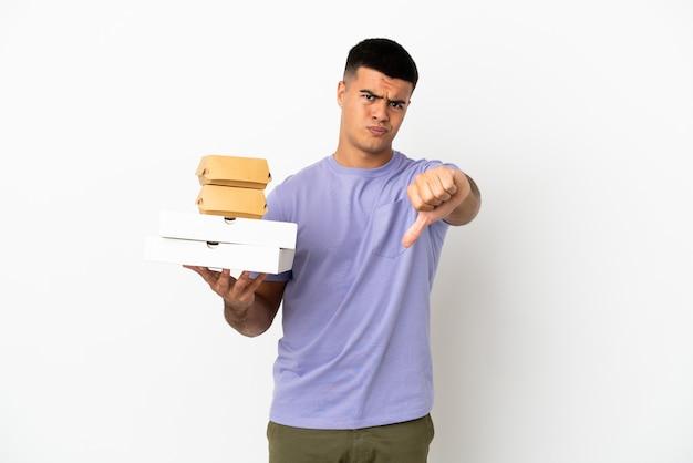 고립 된 흰색 배경 위에 피자와 햄버거를 들고 부정적인 표정으로 엄지손가락을 보여주는 젊은 잘생긴 남자