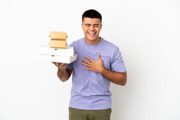 Молодой красавец, держащий пиццу и гамбургеры на изолированном белом фоне, много улыбаясь