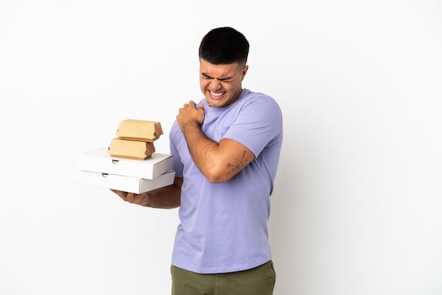 Молодой красавец, держащий пиццу и гамбургеры на изолированном белом фоне, страдает от боли в плече за то, что приложил усилия