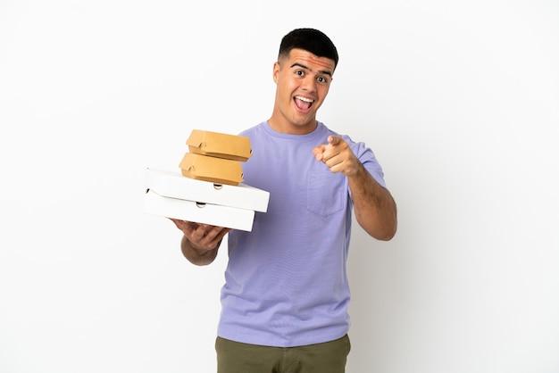 Молодой красавец, держащий пиццу и гамбургеры на изолированном белом фоне, удивился и указал вперед