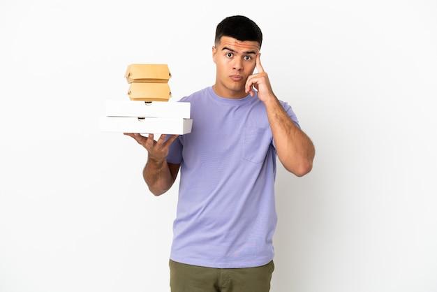 아이디어를 생각하는 고립 된 흰색 배경 위에 피자와 햄버거를 들고 젊은 잘 생긴 남자