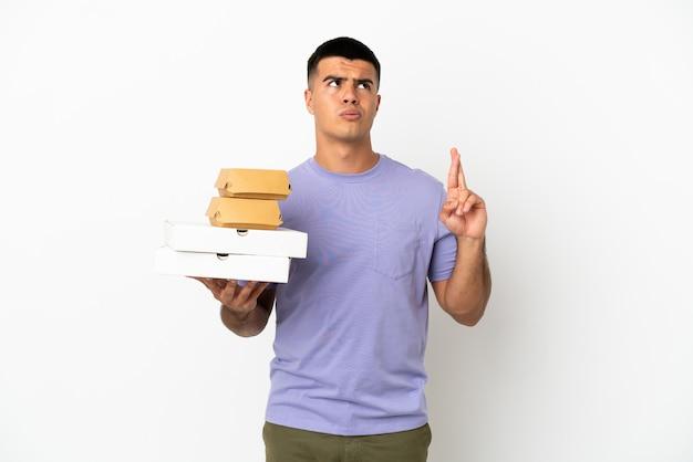 격리된 흰색 배경 위에 피자와 버거를 들고 손가락으로 교차하고 최고를 바라는 젊은 미남