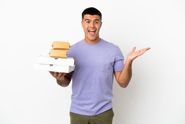 Молодой красавец держит пиццу и гамбургеры на изолированном белом фоне с шокированным выражением лица