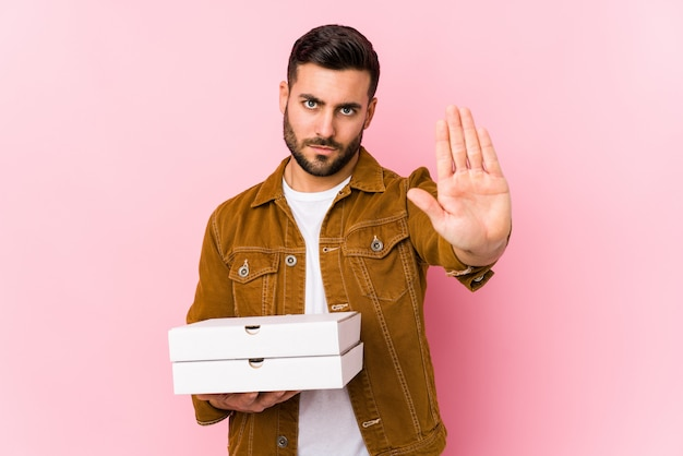 Young handsome man holding pizzas standing with outstretched hand showing stop sign