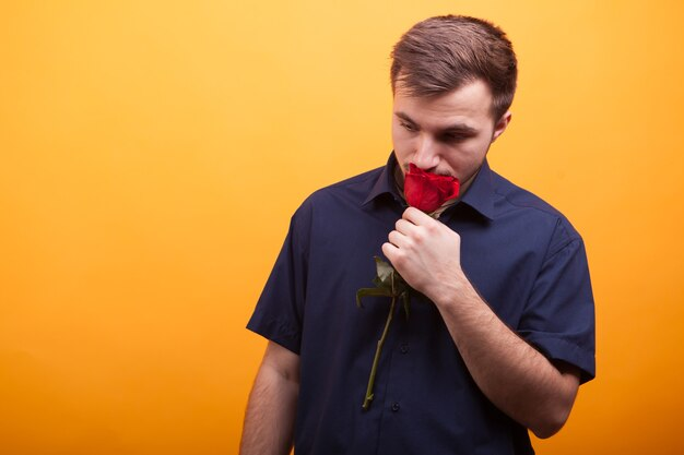 Young handsome man holding red rose in hands over yellow background. romantic man