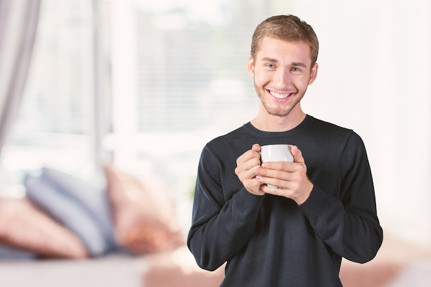 Young handsome man holding warm cup of tea/coffee