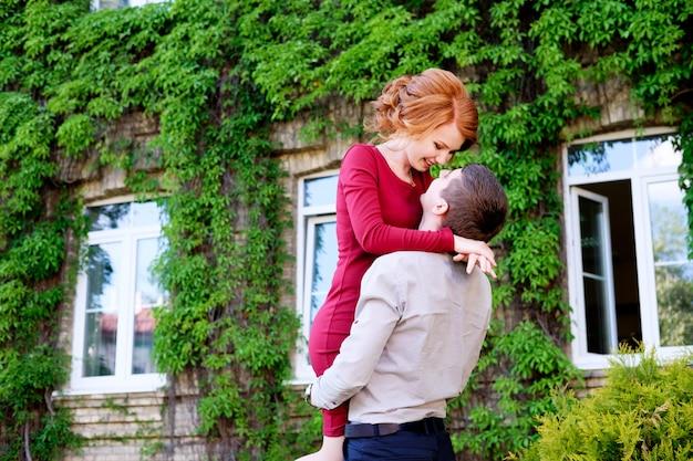 かなり若い赤毛の女性を抱き締める若いハンサムな男