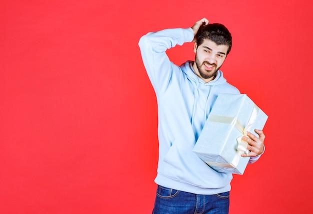 Молодой красавец обнимает упакованную подарочную коробку и кладет руку на голову