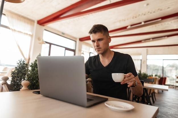 Молодой красавец в черной футболке сидит в винтажном кафе и работает на современном ноутбуке.