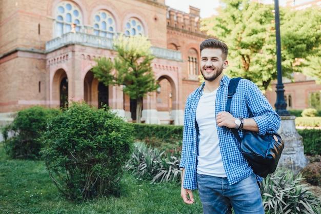 Молодой красавец в синей рубашке с рюкзаком стоит в кампусе и смотрит в сторону