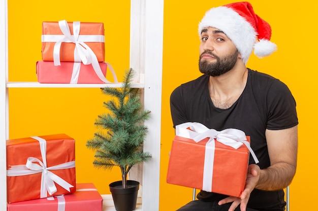 Молодой красавец в шляпе санта-клауса держит поздравительные подарки рядом с елкой. концепция праздников рождества и нового года.
