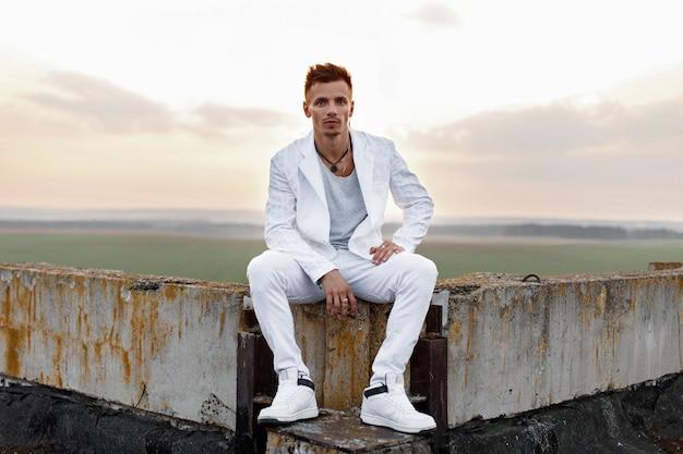 Молодой красавец в стильной белой одежде сидит на крыше