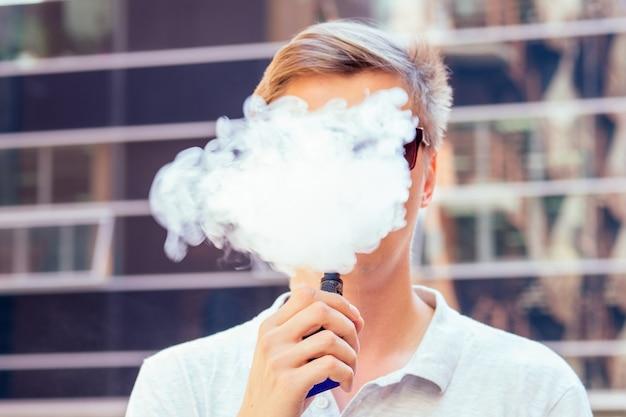 Молодой красавец в белой рубашке курит вейп с облаком дыма на современном фоне