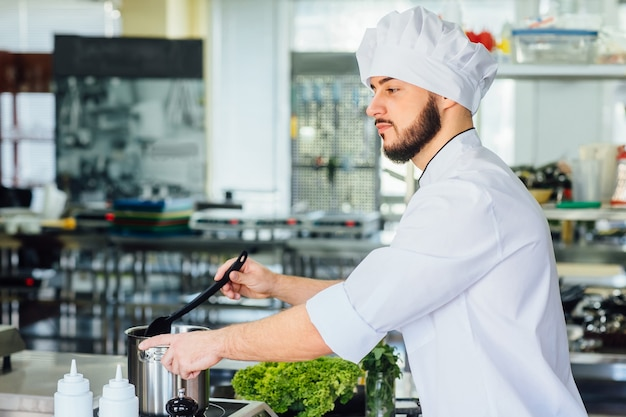 パスタを準備している白い特別なローブを着た若いハンサムな男は、イタリアのスパゲッティのために水を沸騰させます。