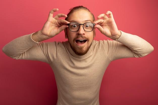 ピンクの壁の上に立って幸せで驚きの正面を見てベージュのタートルネックとメガネの若いハンサムな男