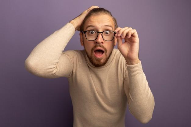 薄紫色の壁の上に立っている彼の眼鏡に触れてカメラをよく見ているベージュのタートルネックと眼鏡の若いハンサムな男