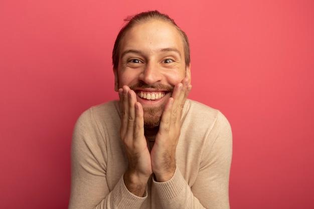 ベージュのタートルネックの若いハンサムな男は幸せで驚きの笑顔を広く