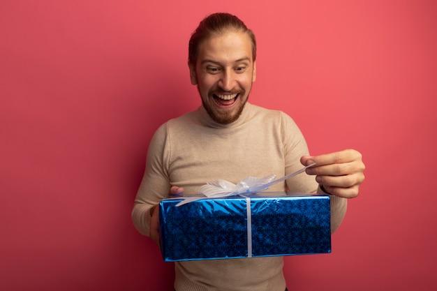 Молодой красавец в бежевой водолазке держит подарочную коробку, пытаясь ее открыть, выглядит счастливым и удивленным, стоя у розовой стены