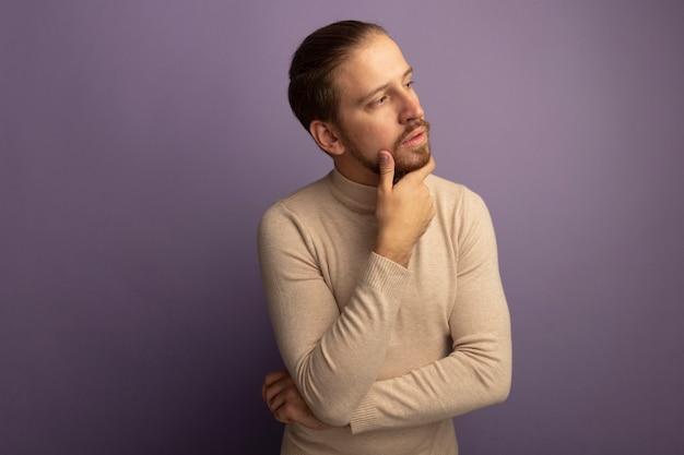 薄紫色の壁の上に立っていると考えて彼のあごに手を置いて脇を見てベージュのタートルネックの若いハンサムな男