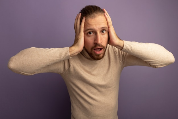 ライラックの壁の上に立っている間違いのために彼の頭の上の手と混同された正面を見てベージュのタートルネックの若いハンサムな男