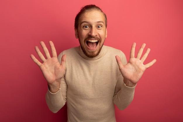 베이지 색 터틀넥에 젊은 잘 생긴 남자가 분홍색 벽 위에 서있는 열린 손바닥을 보여주는 행복하고 흥분된 전면을보고