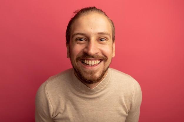 유쾌하게 치아를 보여주는 미소 베이지 색 터틀넥에 젊은 잘 생긴 남자