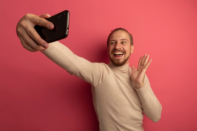 스마트 폰을 사용하는 베이지 색 터틀넥에 젊은 잘 생긴 남자가 행복하고 긍정적 인 손으로 흔들며 셀카를하고