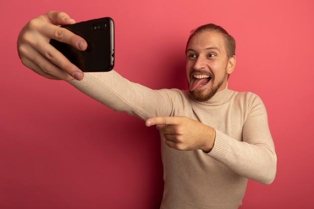 ピンクの壁の上に立っている舌を突き出して自分撮り笑顔をしているスマートフォンを使用してベージュのタートルネックの若いハンサムな男