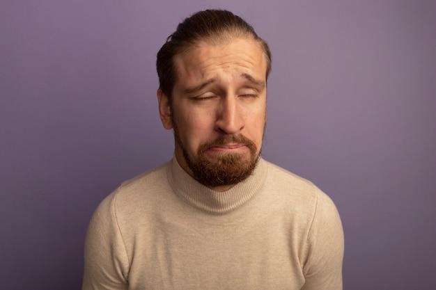 라일락 벽 위에 서있는 슬프고 희망없는 표정으로 베이지 색 터틀넥에 젊은 잘 생긴 남자