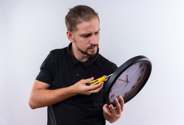 白い背景の上に立っている深刻な顔でそれを修復する壁時計を保持している黒のポロシャツの若いハンサムな男