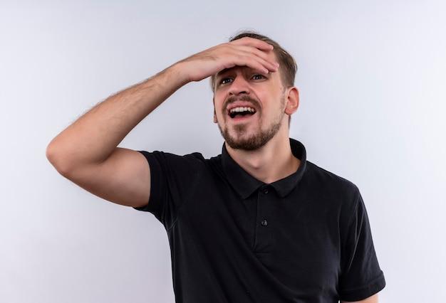 Молодой красавец в черной рубашке поло выглядит смущенным и встревоженным, глядя вверх с рукой на голове, стоя на белом фоне