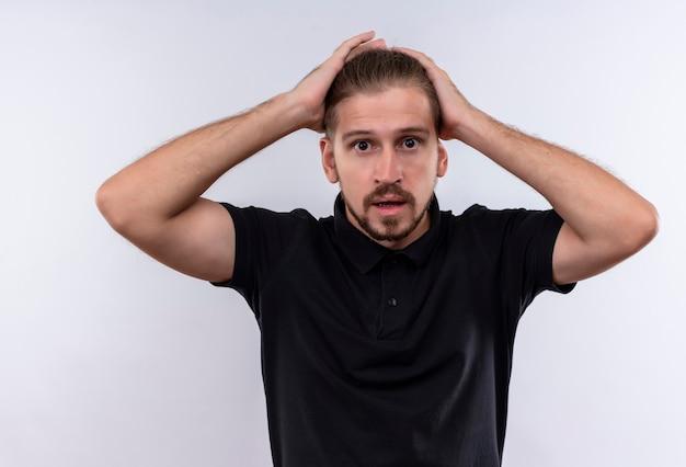 混乱し、白い背景の上に立っている手で彼の頭に触れることを心配している黒のポロシャツで若いハンサムな男