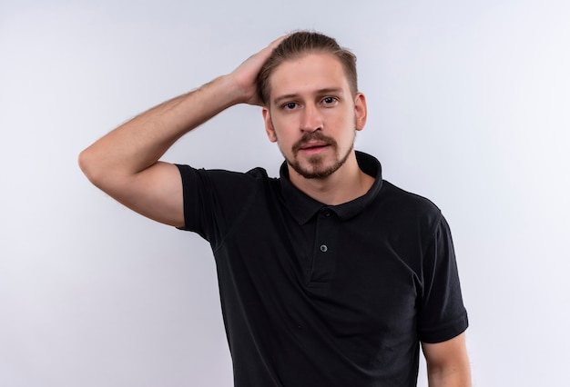 白い背景の上に立っている混乱の感動の頭立っている黒のポロシャツで若いハンサムな男
