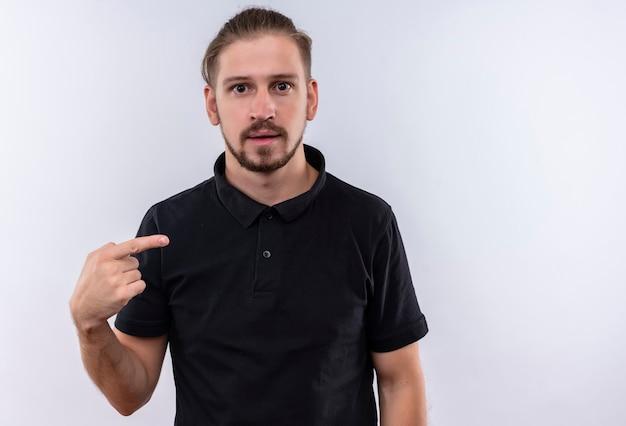 白い背景の上に立っている彼自身を指している怖がって探している黒のポロシャツで若いハンサムな男