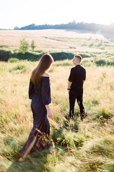 Молодой красавец в черной рубашке и штанах ждет свою красивую женщину, стоя в поле на летнем закате