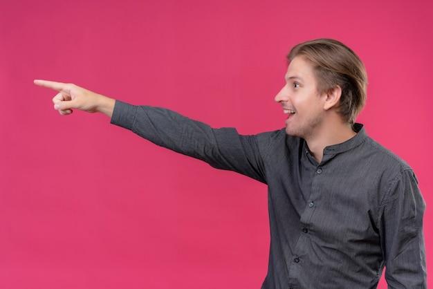側に何かを指している黒いシャツの若いハンサムな男