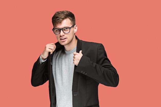 Молодой красивый мужчина в черном костюме и очках, изолированных на красном