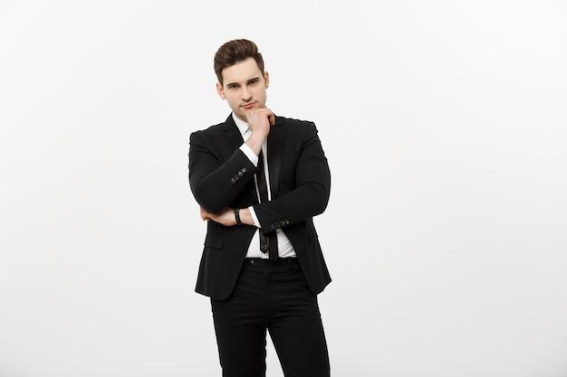 Молодой красавец в черном костюме и очках, глядя на пространство для копирования, улыбается, думает или мечтает, изолированные на белом фоне