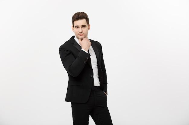 검은 양복과 안경을 쓴 젊고 잘생긴 남자는 흰색 배경에 고립되어 웃고, 생각하거나 꿈꾸는 카피 공간