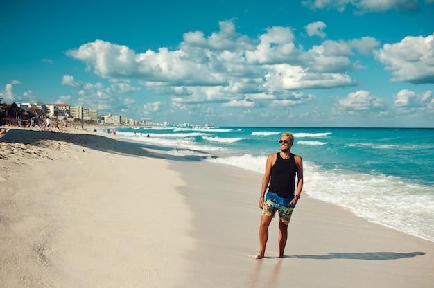Молодой красавец в черной футболке и солнцезащитных очках наслаждается днем на пляже