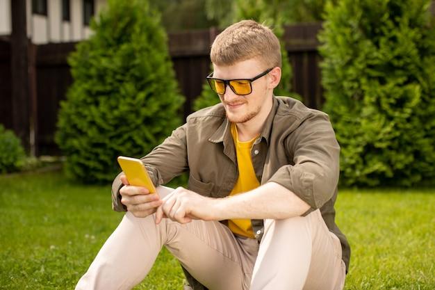 新しいアプリをチェックし、スマートフォンの出会い系サービスでメッセージをテキストメッセージで送信し、友人とチャットし、携帯電話でゲームをしている公園の芝生で休んでいるカジュアルな服装の若いハンサムな男。のんびり、リラックスタイム