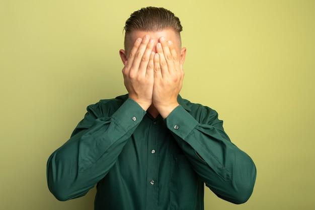 팔이 가벼운 벽에 서서 화가 나서 얼굴을 덮고있는 녹색 셔츠에 젊은 잘 생긴 남자