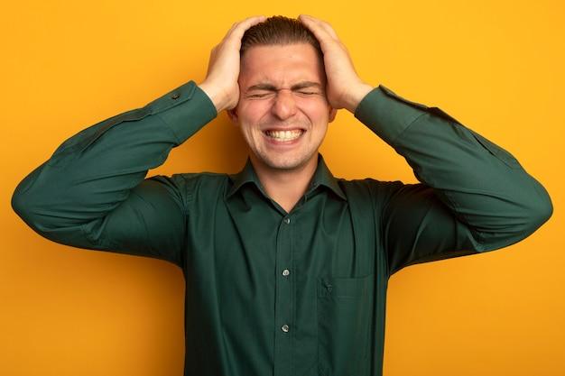 緑のシャツを着た若いハンサムな男は、オレンジ色の壁の上に立っている彼の頭に手をつないで欲求不満と失望