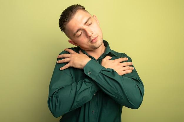 밝은 벽 위에 서있는 긍정적 인 감정을 느끼는 닫힌 눈으로 그의 가슴에 손을 잡고 녹색 셔츠에 젊은 잘 생긴 남자